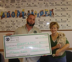 Benefit organizer Lance Hayes presents a check for $2,500 to local charity Adopt A Pet